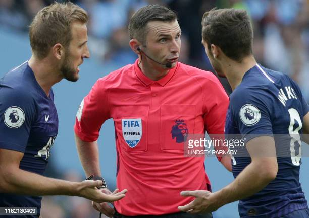 Tottenham Hotspur's English striker Harry Kane and Tottenham Hotspur's English midfielder Harry Winks remonstrate with English referee Michael Oliver...