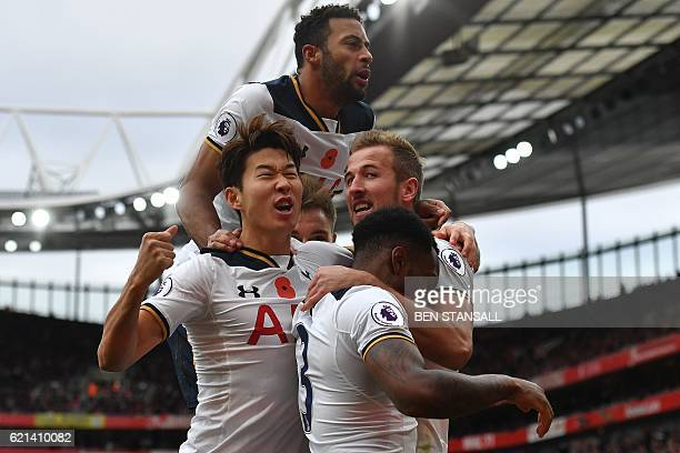 Tottenham Hotspur's English striker Harry Kane celebrates scoring his team's first goal from the penalty spot with Tottenham Hotspur's Belgian...