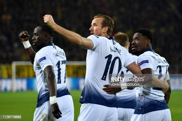 Tottenham Hotspur's English striker Harry Kane celebrates scoring the opening goal with his teammates Ivorian defender Serge Aurier and midfielder...