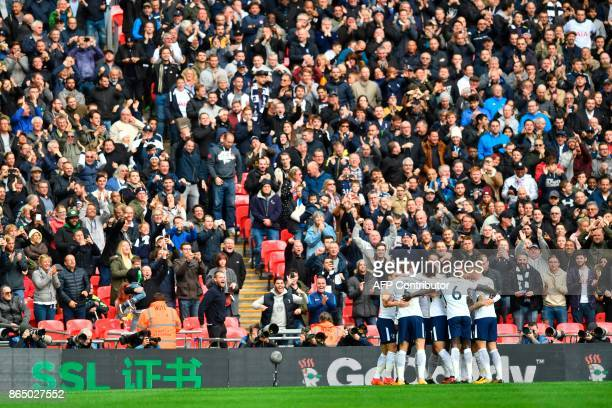 Tottenham Hotspur's English striker Harry Kane celebrates with teammates after scoring the opening goal of the English Premier League football match...