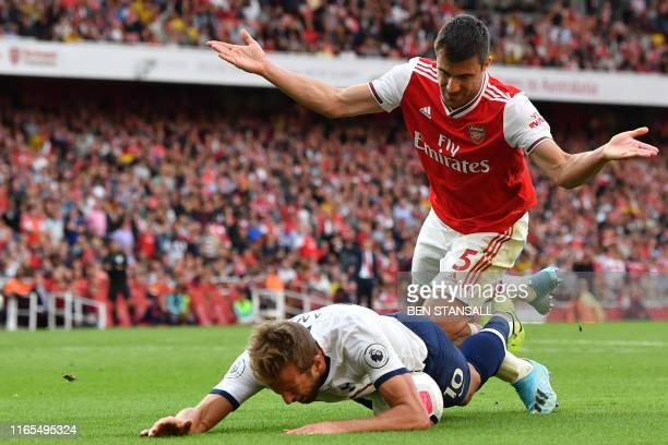 Tottenham Hotspur's English striker Harry Kane falls in the area under pressure from Arsenal's Greek defender Sokratis Papastathopoulos but no...