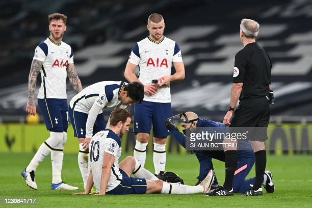 Tottenham Hotspur's English striker Harry Kane gets attention from the physio after a challenge during the English Premier League football match...