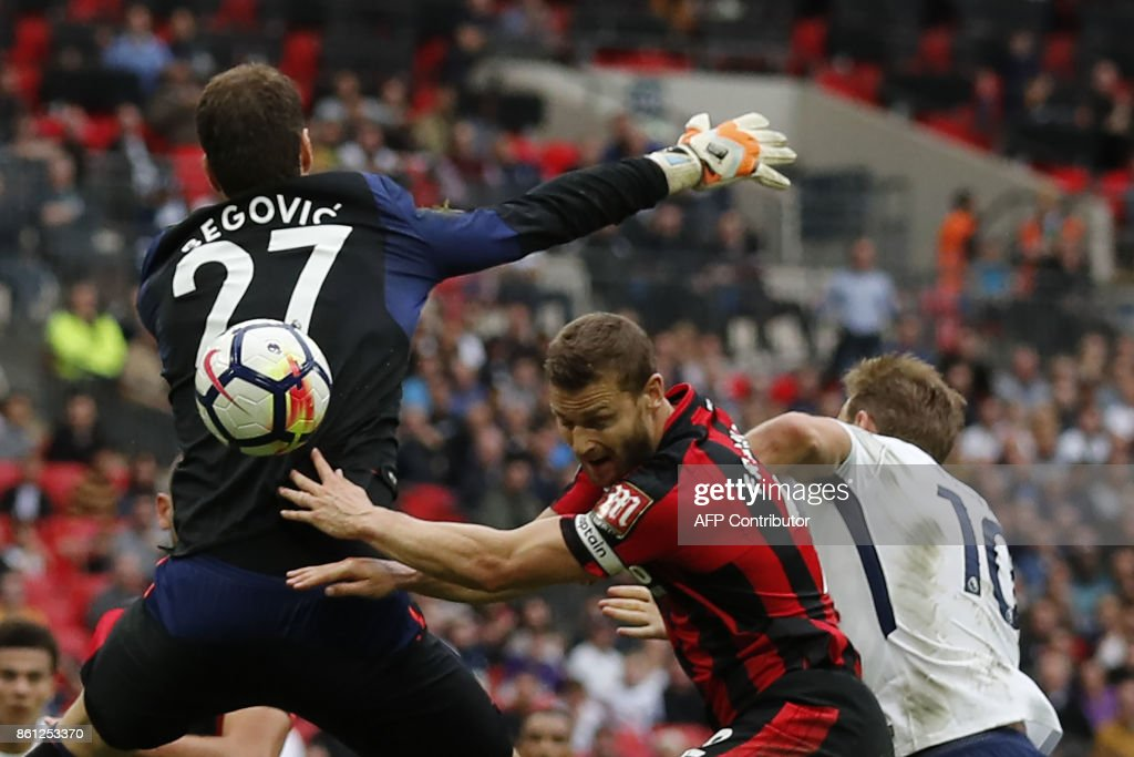 Tottenham Hotspur's English striker Harry Kane (R) heads the ball to goal past Bournemouth's Bosnian-Herzegovinian goalkeeper Asmir Begovic (L) but disallowed during the English Premier League football match between Tottenham Hotspur and Bournemouth at Wembley Stadium in London, on October 14, 2017. / AFP PHOTO / Adrian DENNIS / RESTRICTED TO EDITORIAL USE. No use with unauthorized audio, video, data, fixture lists, club/league logos or 'live' services. Online in-match use limited to 75 images, no video emulation. No use in betting, games or single club/league/player publications. /