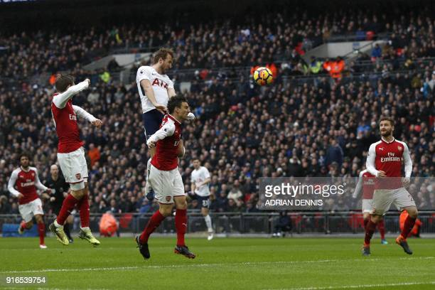Tottenham Hotspur's English striker Harry Kane heads the ball to score the opening goal during the English Premier League football match between...