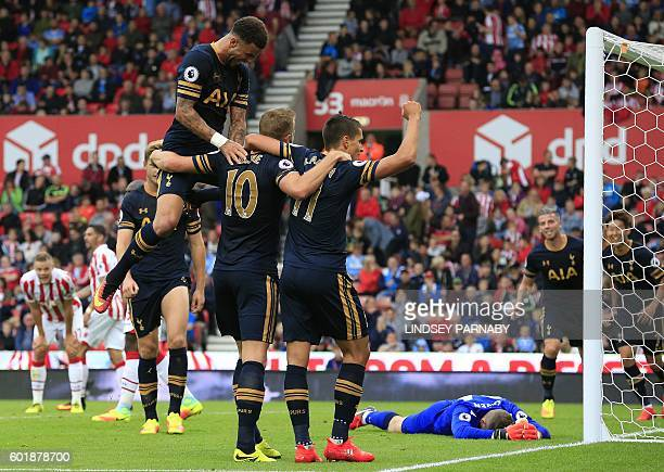 Tottenham Hotspur's English striker Harry Kane is mobbed by teammates after scoring his team's fourth goal during the English Premier League football...