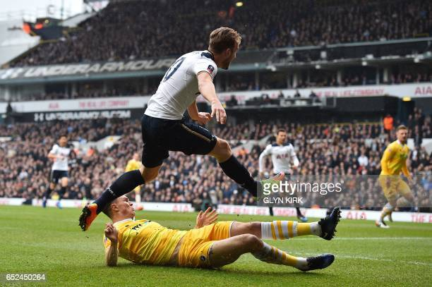 Tottenham Hotspur's English striker Harry Kane is tackled by Millwall's English defender Jake Cooper as he shoots at goal during the English FA Cup...