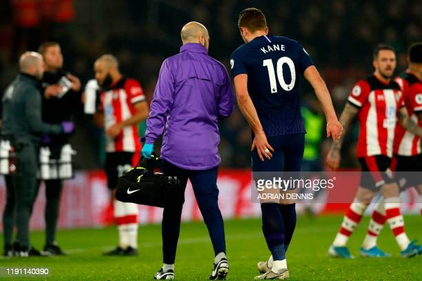 Tottenham Hotspur's English striker Harry Kane leaves the pitch having picked up an injury during the English Premier League football match between...
