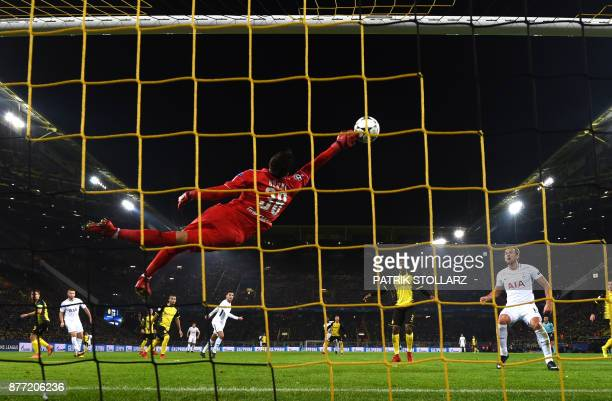 TOPSHOT Tottenham Hotspur's English striker Harry Kane looks on as Dortmund's Swiss goalkeeper Roman Buerki flys through the air to make a save...