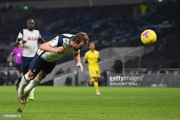 Tottenham Hotspur's English striker Harry Kane scores his team's first goal with a diving header during the English Premier League football match...