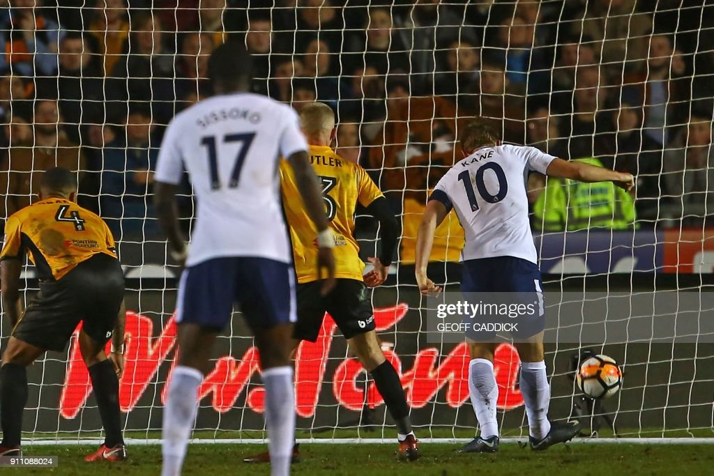 Tottenham Hotspur's English striker Harry Kane (R) scores their first goal during the English FA Cup fourth round football match between Newport County and Tottenham Hotspur at Rodney Parade in Newport, in south Wales, on January 27, 2018. / AFP PHOTO / Geoff CADDICK / RESTRICTED TO EDITORIAL USE. No use with unauthorized audio, video, data, fixture lists, club/league logos or 'live' services. Online in-match use limited to 75 images, no video emulation. No use in betting, games or single club/league/player publications. /