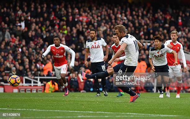 Tottenham Hotspur's English striker Harry Kane shoots from the penalty spot to scores his team's first goal during the English Premier League...