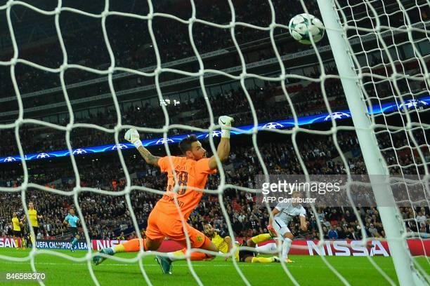 Tottenham Hotspur's English striker Harry Kane shoots past Borussia Dortmund's Swiss goalkeeper Roman Buerki to score their seconf goal during the...