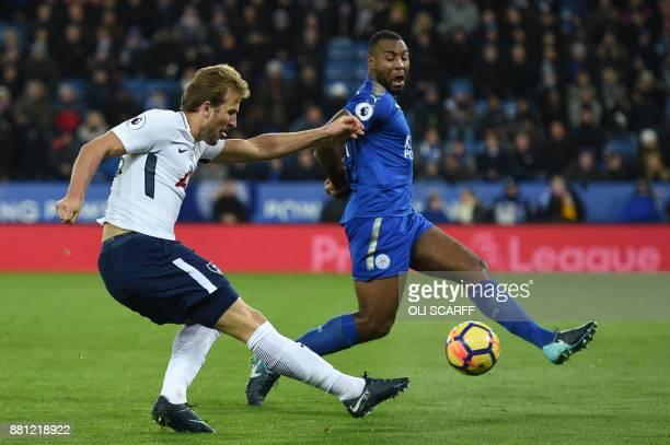 Tottenham Hotspur's English striker Harry Kane shoots past Leicester City's Englishborn Jamaican defender Wes Morgan during the English Premier...