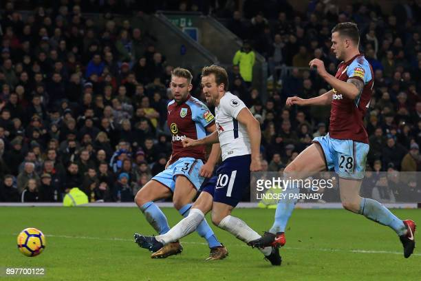 Tottenham Hotspur's English striker Harry Kane shoots to score his and Tottenham's second goal under pressure from Burnley's English defender Charlie...