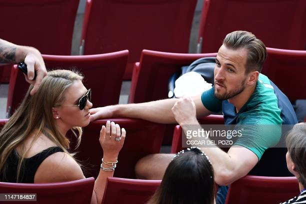 Tottenham Hotspur's English striker Harry Kane sits next to his partner his partner Katie Goodland after a training session at the Wanda...