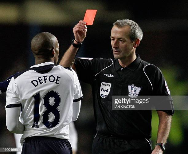 Tottenham Hotspur's English striker Jermain Defoe is shown the red card by referee Martin Atkinson after a challenge on Aston Villa's Welsh defender...