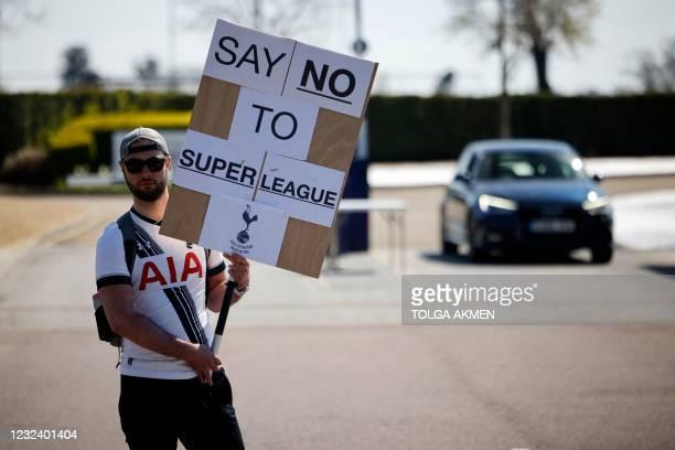Tottenham Hotspur's fan holds an anti-European Super League placard has he demonstrates outside the English Premier League football club's training...
