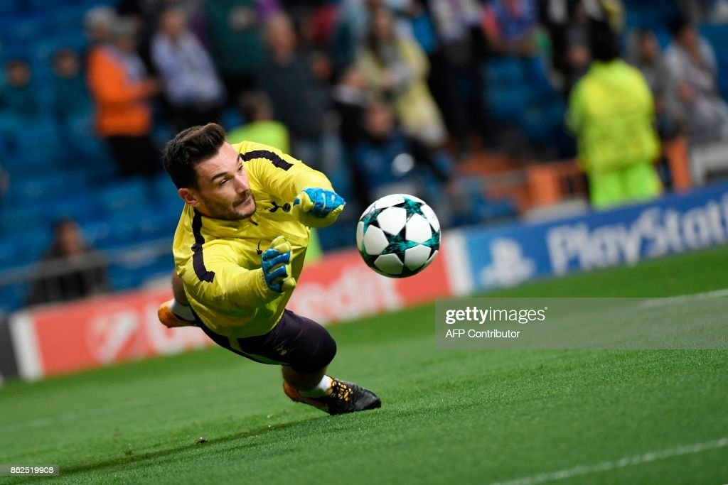 TOPSHOT - Tottenham Hotspur's French goalkeeper Hugo Lloris dives for the ball sduring a warm up before the UEFA Champions League group H football match Real Madrid CF vs Tottenham Hotspur FC at the Santiago Bernabeu stadium in Madrid on October 17, 2017. /
