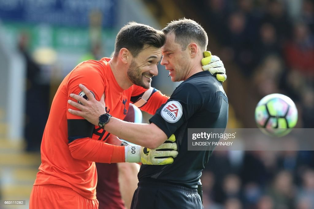 Tottenham Hotspur's French goalkeeper Hugo Lloris (L) shares a moment with English referee Stuart Attwell during the English Premier League football match between Burnley and Tottenham Hotspur at Turf Moor in Burnley, north west England on April 1, 2017. Tottenham won the game 2-0. / AFP PHOTO / Lindsey PARNABY / RESTRICTED TO EDITORIAL USE. No use with unauthorized audio, video, data, fixture lists, club/league logos or 'live' services. Online in-match use limited to 75 images, no video emulation. No use in betting, games or single club/league/player publications. /