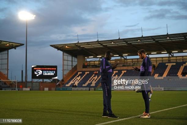 Tottenham Hotspur's French midfielder Moussa Sissoko and Tottenham Hotspur's Belgian defender Jan Vertonghen use their mobile phones as they stand on...