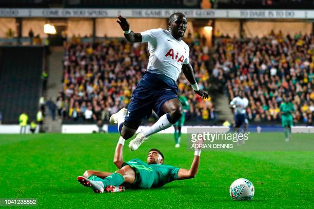 Tottenham Hotspur's French midfielder Moussa Sissoko hurdles a challenge from Watford's Moroccanborn Italian defender Adam Masina during the English...