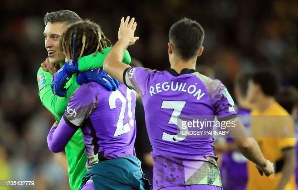 Tottenham Hotspur's Italian goalkeeper Pierluigi Gollini celebrates with Tottenham Hotspur's English midfielder Dele Alli and Tottenham Hotspur's...
