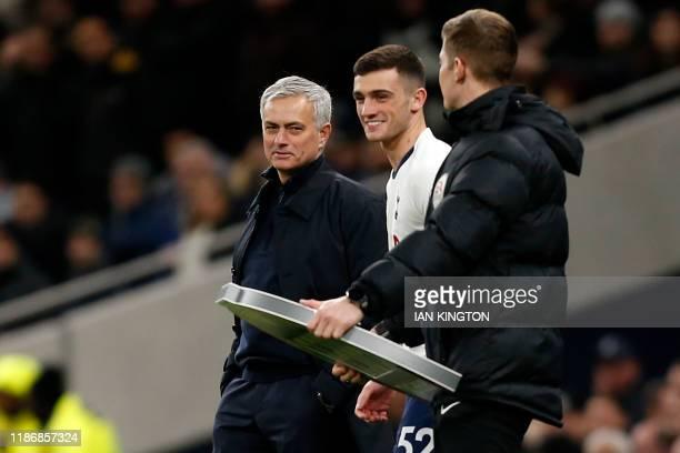 Tottenham Hotspur's Portuguese head coach Jose Mourinho chats with Tottenham Hotspur's Irish striker Troy Parrott as he prepares to come on during...