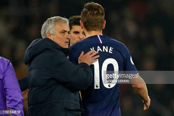 Tottenham Hotspur's Portuguese head coach Jose Mourinho consoles Tottenham Hotspur's English striker Harry Kane as he leaves the pitch having picked...