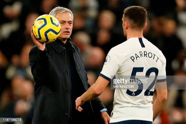 Tottenham Hotspur's Portuguese head coach Jose Mourinho presents Tottenham Hotspur's Irish striker Troy Parrott with the match ball to mark his...