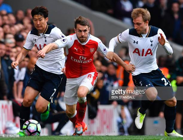 Tottenham Hotspur's South Korean striker Son HeungMin and Tottenham Hotspur's Danish midfielder Christian Eriksen challenge Arsenal's Welsh...