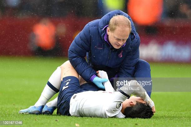 Tottenham Hotspur's South Korean striker Son HeungMin holds his arm as he lies injured on the pitch during the English Premier League football match...