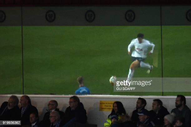 Tottenham Hotspur's South Korean striker Son HeungMin is reflected in a window during the English FA Cup fifth round football match between Rochdale...