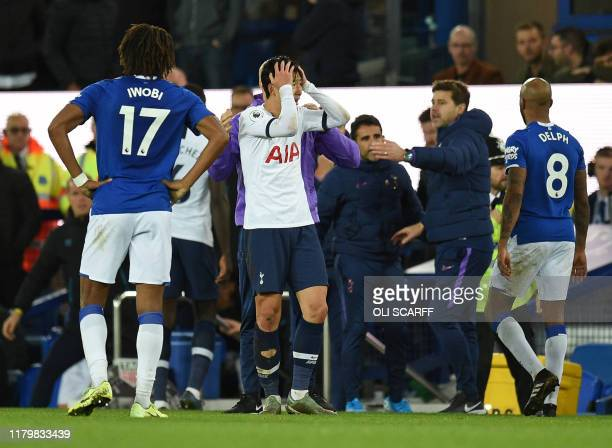 Tottenham Hotspur's South Korean striker Son Heung-Min reacts after his involvement in an incident that resulted in an injury to Everton's Portuguese...