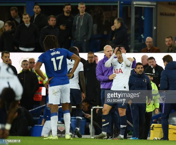 TOPSHOT Tottenham Hotspur's South Korean striker Son HeungMin reacts after his involvement in an incident that resulted in an injury to Everton's...