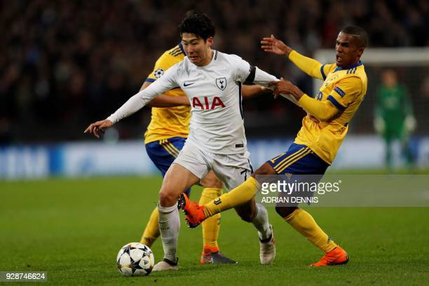 Tottenham Hotspur's South Korean striker Son HeungMin squeezes between Juventus' Brazilian midfielder Douglas Costa and Juventus' German midfielder...