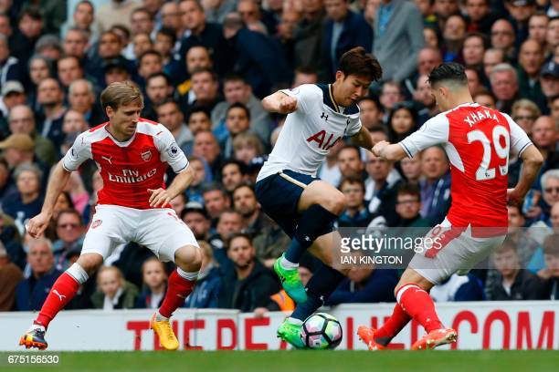 Tottenham Hotspur's South Korean striker Son HeungMin vies with Arsenal's Swiss midfielder Granit Xhaka during the English Premier League football...