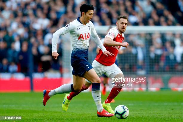 Tottenham Hotspur's South Korean striker Son HeungMin vies with Arsenal's Welsh midfielder Aaron Ramsey during the English Premier League football...