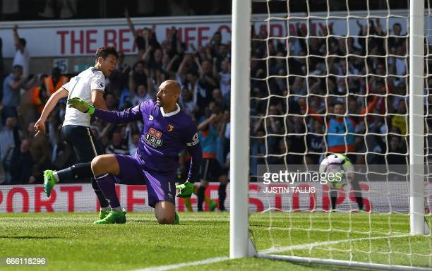 Tottenham Hotspur's South Korean striker Son HeungMin watches the ball pass Watford's Brazilian goalkeeper Heurelho Gomes and score his team's fourth...