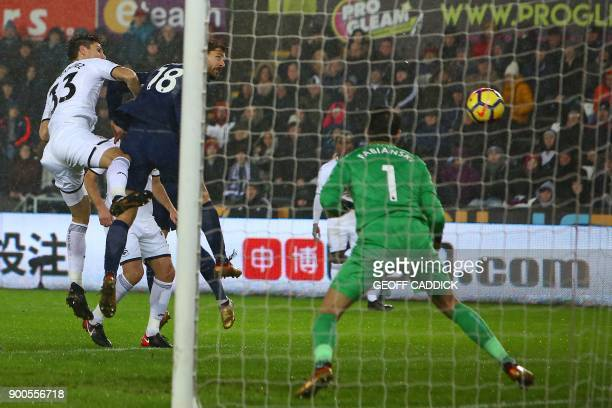 Tottenham Hotspur's Spanish striker Fernando Llorente heads past Swansea City's Polish goalkeeper Lukasz Fabianski for Tottenham's first goal during...