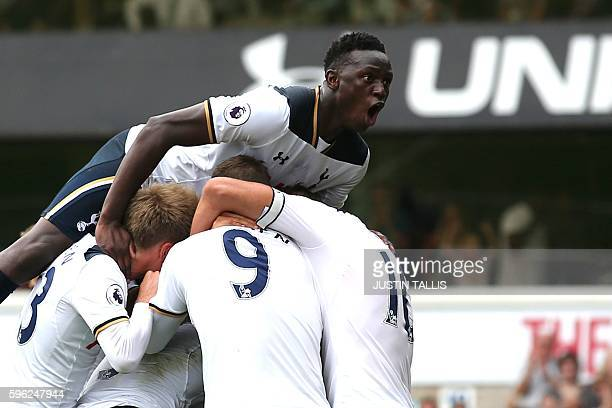 Tottenham Hotspur's Victor Wanyama jumps onto teammates as they celebrate a goal by English defender Danny Rose during the English Premier League...