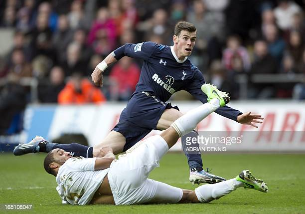 Tottenham Hotspur's Welsh midfielder Gareth Bale shoots past Swansea City's Englishborn Welsh defender Ashley Williams during the Premiership match...