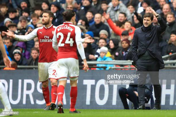 Tottenham manager Mauricio Pochettino and Shkodran Mustafi of Arsenal react to referee decisions during the Premier League match between Tottenham...