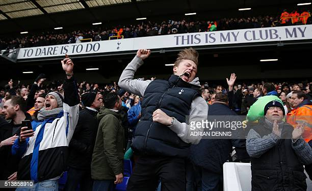 Tottenham supporters celebrate their team's first goal during the English Premier League football match between Tottenham Hotspur and Arsenal at...