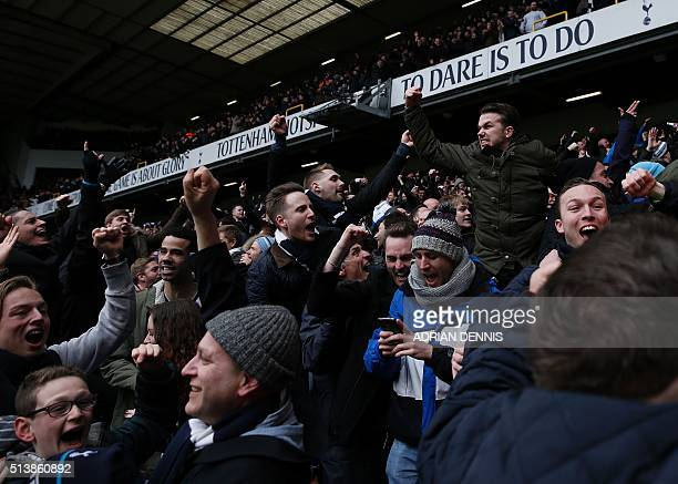 Tottenham supporters celebrate their team's second goal during the English Premier League football match between Tottenham Hotspur and Arsenal at...