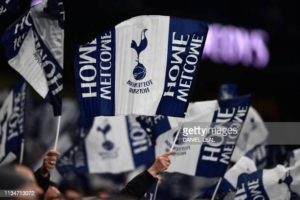 Tottenham supporters wave flags inside the ground ahead of the first Premier League game to be played at their new stadium the English Premier League...