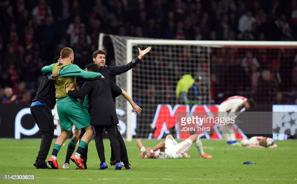 Tottenham's Argentine coach Mauricio Pochettino celebrates next to Ajax players reacting on the ground after Tottenham won the UEFA Champions League...