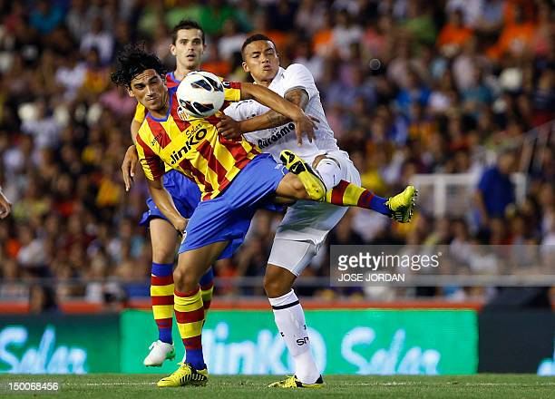 Tottenham's Jermain Jenas vies for the ball with Valencia's Argentinian midfielder Alberto Costa during the friendly football match between Valencia...