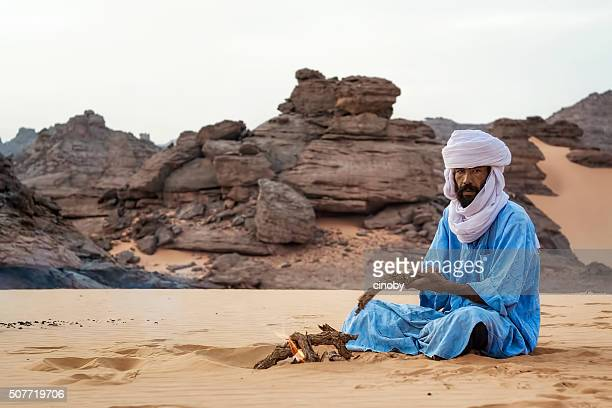 Touareg makes a campfire in the Akakus Mountains, Libya desert