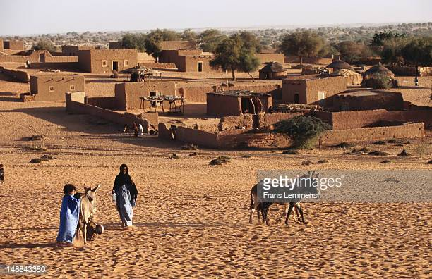 Touareg woman with child and donkeys.