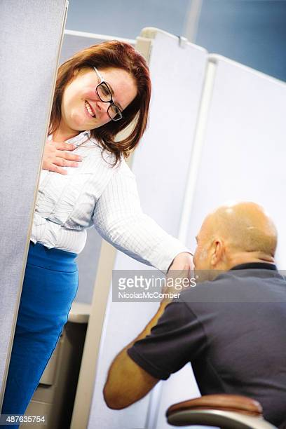 Touched female cubicle worker receives kiss by colleague